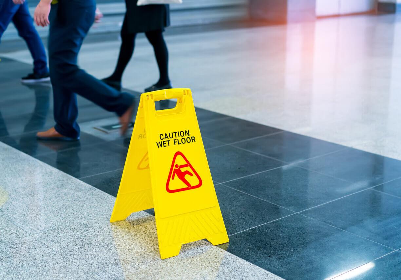 Wet floor sign in the middle of floor.