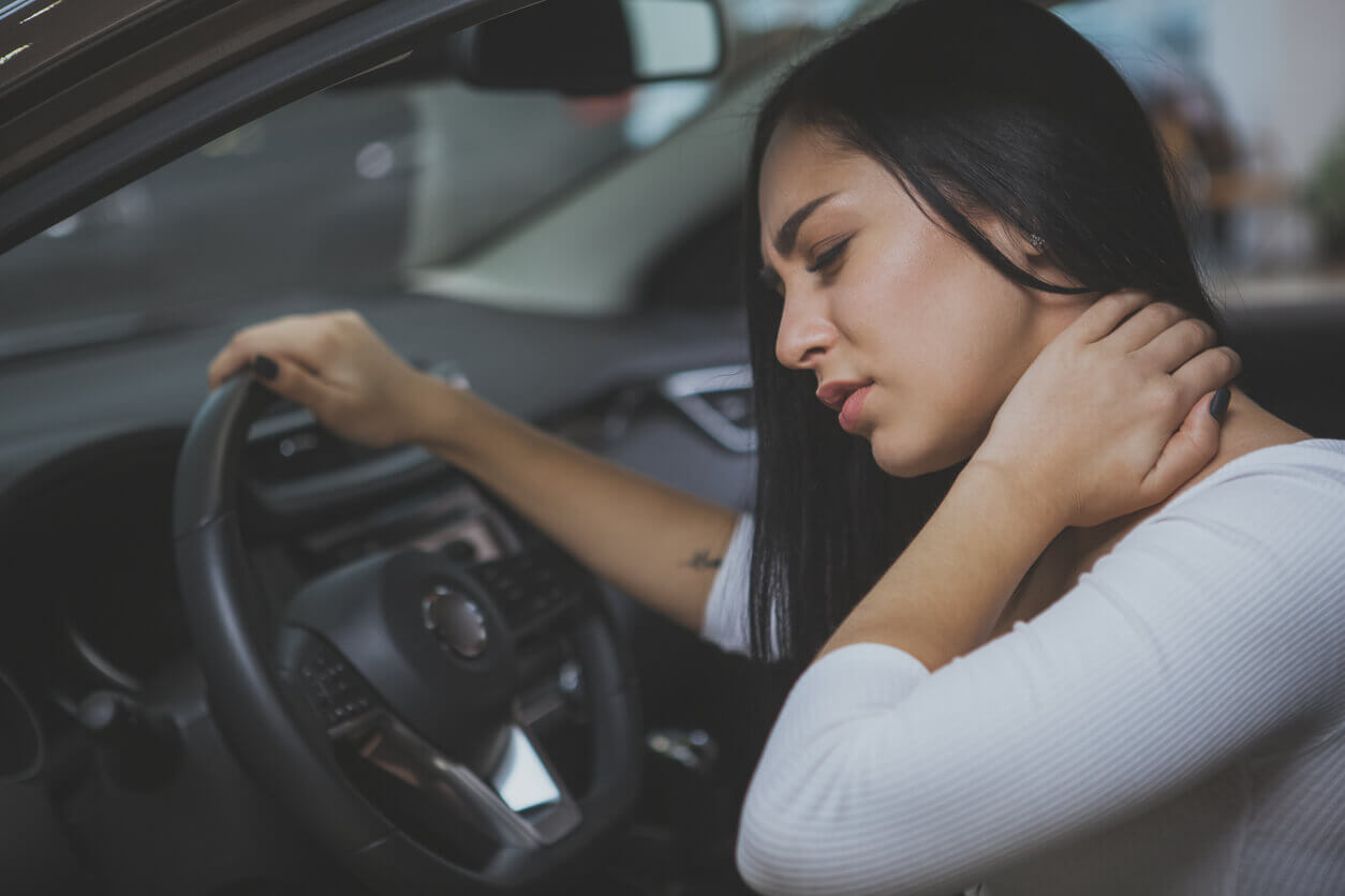 Woman rubbing her neck after a car accident.
